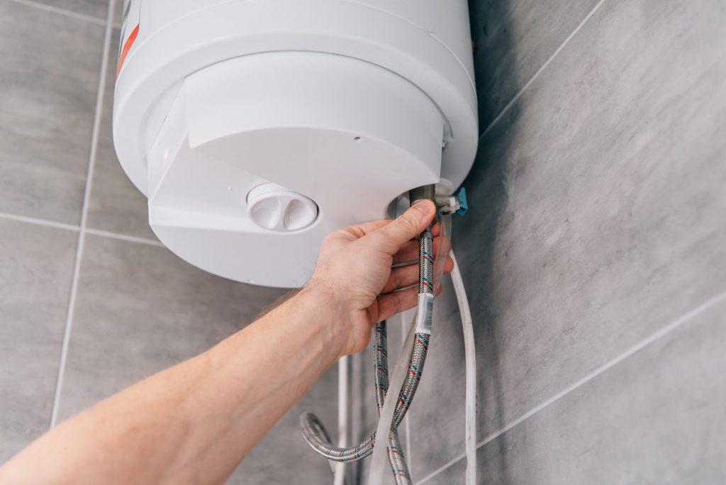 cropped shot of male plumber repairing electric boiler in bathroom