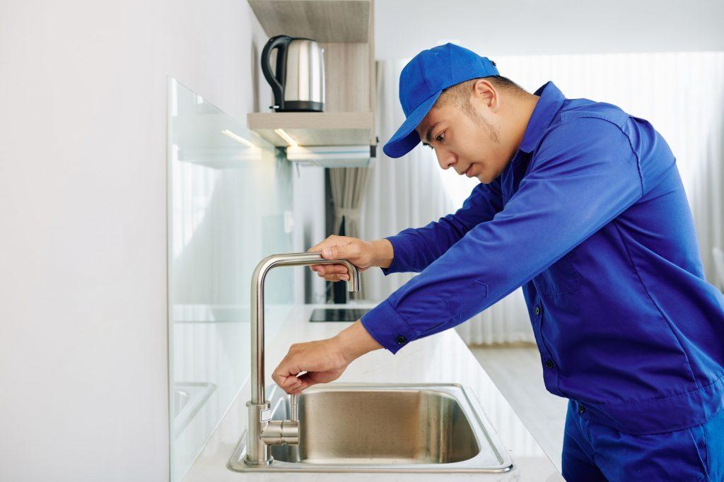Repairman fixing water tap
